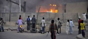 875659_people-watch-as-smoke-rises-from-the-police-headquarters-after-it-was-hit-by-a-blast-in-nigeria-s-northern-city-of-kano