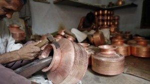 Workers use hammers to form copper pitchers inside a workshop in the western Indian city of Ahmedabad