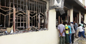 Residents peer into a building bombed by unidentified gunmen who attacked the coastal Kenyan town of Mpeketoni