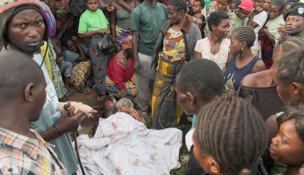 des-personnes-se-tiennent-pres-d-une-fosse-apres-le-massacre-de-22-personnes-pa